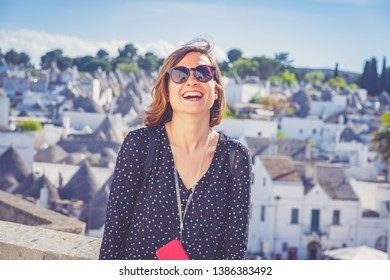 happy tourist take selfie photo in Alberobello town, Apulia, southern Italy. The town of alberobello is famous for the typical trulli houses