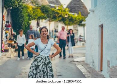 happy tourist take selfie photo in Alberobello town, Apulia, southern Italy. The town of alberobello is famous for the typical white trulli houses. Unidentified tourits walking in the city