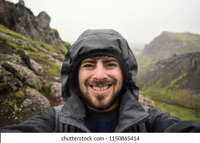 Happy tourist taking selfie in the rain while hiking in Iceland
