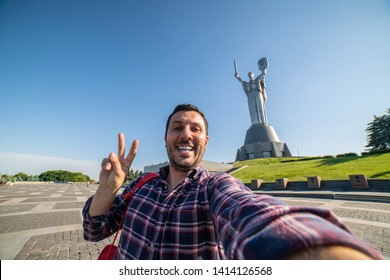 Happy tourist traveling in Ukraine taking selfie in front of the mother Motherland monument in Kiev. Historical sights of Ukraine. The monument is decorated to the Victory Day in the Second World War