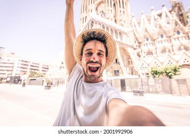 Happy tourist visiting La Sagrada Familia, Barcelona Spain - Smiling man taking a selfie outdoor on city street - Tourism and vacations concept