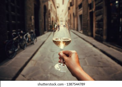 Happy tourist walking on narrow streets with white wine glass in hand. Enjoying life concept.