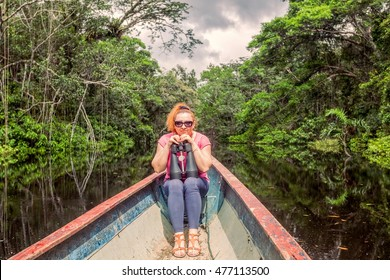 Happy Tourist Woman In A Canoe With High Power Binocular In Amazonian Jungle, National Park Cuyabeno, South America