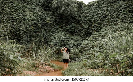 Happy tourist woman Jungle Trekking  on holiday relaxing Concept. hipster asian woman exploring dense tropical jungle and rainforest Outdoor photo . model posing and smiling  during Summer travel .