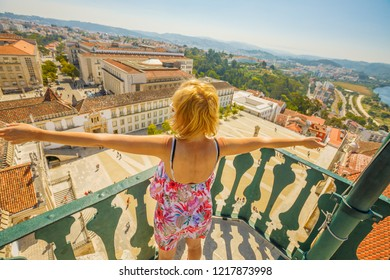Happy tourist woman with open arms admiring Coimbra panorama from top of bell Clock Tower. Female tourist enjoys in Portugal, Europe. Coimbra city skyline and University courtyard.