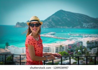 Happy tourist woman with straw sunhat looking to the mediterranean sea and enjoying the blue and scenic seascape in Altea, Alicante, Spain. Living coral dress, color of the year