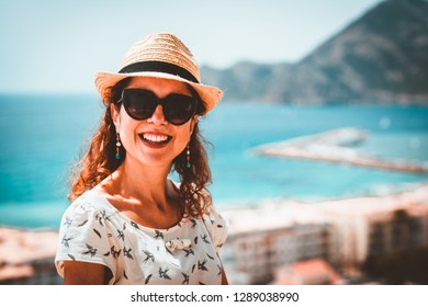 Happy tourist woman with straw sunhat looking to the mediterranean sea and enjoying the blue and scenic seascape in Altea, Alicante, Spain. Teal and orange look.