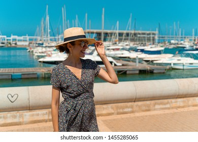 Happy tourist woman with straw sunhat looking to the mediterranean sea and enjoying the blue and scenic Denia marina Port , Alicante, Spain. Teal and orange style.