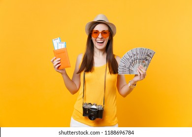 Happy tourist woman in summer casual clothes holding lots of dollars money, passport isolated on yellow orange background. Female traveling abroad to travel on weekends getaway. Air flight concept
