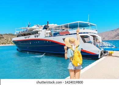 Happy tourist woman traveler with backpack and hat standing on a sea shore and waiting for cruise ship or ferry boat. Transportation and travel concept