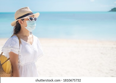 Happy tourist woman wearing surgical face mask  enjoy beautiful sea and white sand at tropical beach. protection Coronavirus disease (Covid-19) infection. New Normal, travel, vacation and holiday