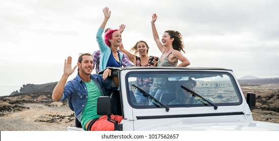 Happy tourists friends doing excursion in desert on convertible 4x4 car - Young people having fun traveling together - Friendship, youth lifestyle and vacation concept - Focus on blond hair girl
