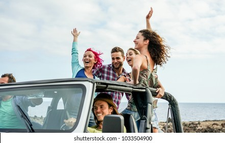 Happy tourists friends doing excursion in desert on convertible 4x4 car - Young people having fun traveling together - Friendship, youth lifestyle and vacation concept - Focus on left woman