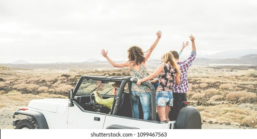 Happy tourists friends doing excursion on desert in convertible 4x4 car - Young people having fun traveling together - Friendship, tour, youth lifestyle and vacation concept - Main focus on bodies