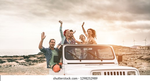 Happy tourists friends doing excursion on desert in convertible 4x4 car - Young people having fun traveling together - Friendship, tour, youth lifestyle and vacation concept - Focus on center faces