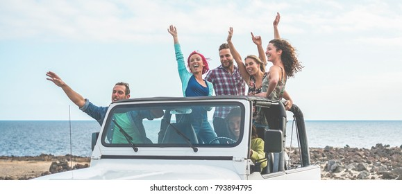 Happy tourists friends doing excursion in desert on convertible jeep car - Young people having fun traveling together - Friendship, youth lifestyle and vacation concept - Focus on guys with hands up