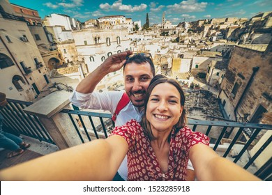 Happy tourists in Matera taking selfie photo smiling with sassi of Matera panorama in background, Capital of Culture 2019, Basilicata, Italia
