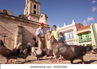 Happy tourists on holiday in Cuba. Hispanic people traveling in Havana. Grandpa and grandson feeding birds, giving food to pigeons in square