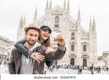 Happy tourists taking a self portrait with phone in front of Duomo cathedral,Milan - Couple traveling in Italy