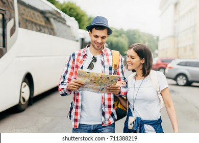 Happy tourists or travellers looking with happy expression in map, being glad to see one more place to reach, having good mood after wonderful trip on bus, going sightseeing, having trip together