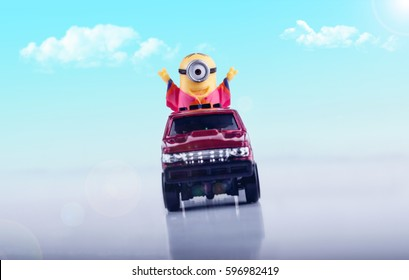 Happy Toy Minion Ride Toy minion, in a red toy truck, smiling and having a great time. Light blue sky and clouds in the background with a white gradient surface.