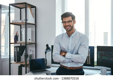 Happy trader. Cheerful businessman in formal clothes and eyeglasses is keeping arms crossed, smiling and looking at camera while standing at office.