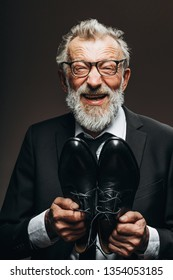 Happy transformation of a poor homeless old tramp into a well-dressed gentleman in suit who is beaming with joy and hapiness enjoying his new leather shoes.