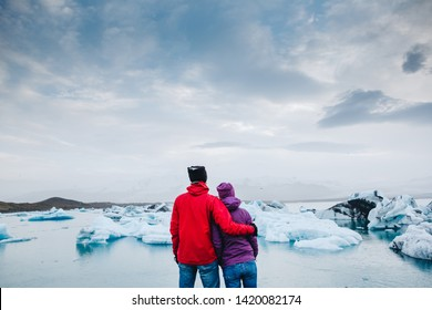 Happy travel couple enjoying the view on Iceland Jokulsarlon glacial lagoon
