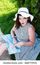 Happy travel woman look map sitting on grass in striped dress
