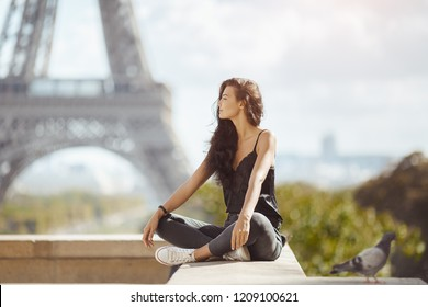 Happy travel woman near the Eiffel tower, Paris. Travel tourist girl on vacation resting happy outdoors. Attractive young romantic woman sitting against beautiful view of Paris. Gorgeous mixed race