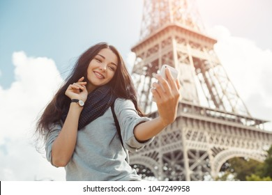 Happy travel woman taking funny selfie with her mobile phone near the Eiffel tower, Paris. Portrait of travel tourist girl on vacation walking happy outdoors. Attractive young romantic woman standing