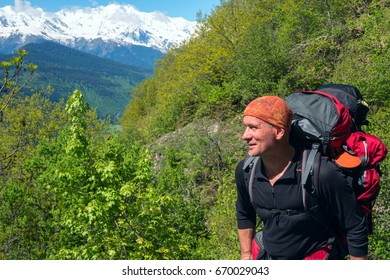 Happy traveler among green trees on the background of snow-capped peaks. Wonderful sunny day in the mountains.