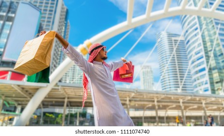 Happy traveler Arabian man hand holding multicolored shoping bags in city downtown, Traveling and joy shopping trip in Asia, lifestyle Asian tourist on summer holiday vacation concept, Crop for banner