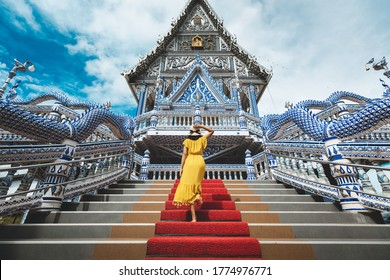 Happy traveler asian woman with dress travel in Wat Pak Nam Khaem Nu temple, Chanthaburi, Thailand