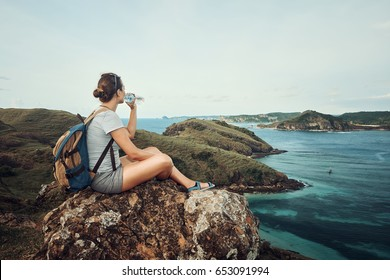 happy traveler with backpack and bottle of water standing on top of mountain and enjoying valley view with raised hands. Mountains landscape, travel to Asia, happiness emotion, summer holiday concept