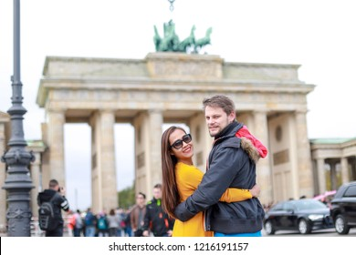 Happy traveler couple at famous Brandenburg Gate landmark of Berlin city, Germany they hugging each other looking at camera and smiling
