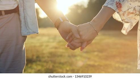 Happy traveler couple. Loving couple holding hands close-up.