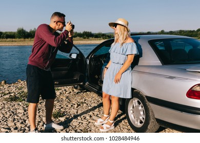 Happy traveler couple standing near car open trunk and watch the sunrise