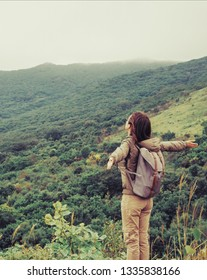 Happy traveler explorer young woman with backpack standing with raised arms and enjoying a beautiful nature.