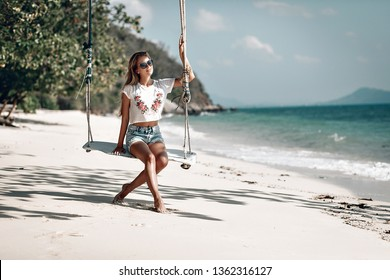 Happy traveler female in a white t-shirt and jeans short relaxing on swing and looking beautiful nature landscape , Tourist sea beach Thailand, Asia, Summer holiday vacation travel trip