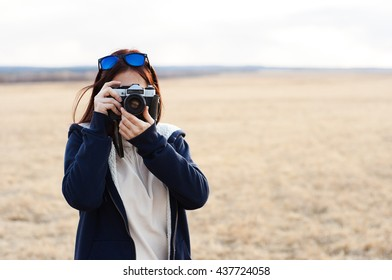 Happy traveler girl photographing field in bright sun rays, interesting profession, travel and tourism concept