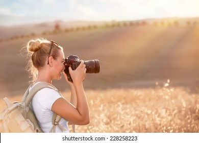 Happy traveler girl photographing ripe wheat field in bright sun rays, autumn harvest season, interesting profession, travel and tourism concept