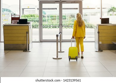 Happy traveler going to the gates, flight in airport. Woman with yellow suitcase from the back in waiting room