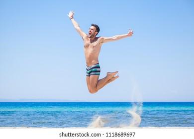 Happy traveler jumping happy at the beach, summer holiday