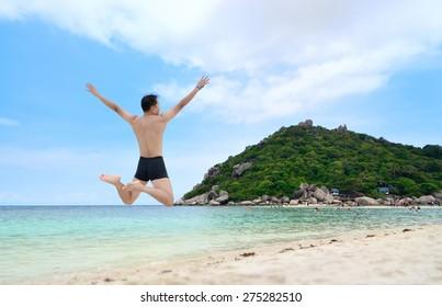 Happy traveler jumping on the beach, ko nangyuan, THAILAND.