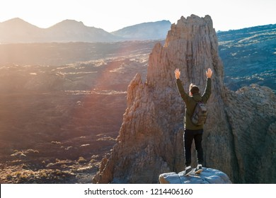 Happy traveler man with hands up enjoying sunset in mountains standing on the cliff edge, Tenerife, Spain. Travel concept