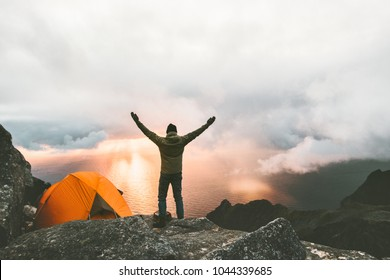 Happy traveler man on the top of mountain raised hands enjoying sunset view near tent camping outdoor Travel adventure lifestyle success concept hiking active vacations