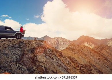 Happy Traveler man sitting on his car on mountains top. 4x4 travel trekking