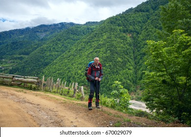 Happy traveler on the mountain road on the background of green hills in cloudy day.