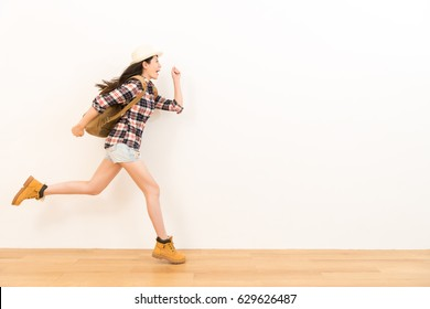 happy traveler on wooden floor showing performance of posture of running excited with white wall background for travel advertising.